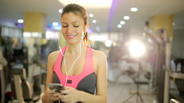 smiling woman with smartphone on treademill - treadmill stock videos and b-roll footage