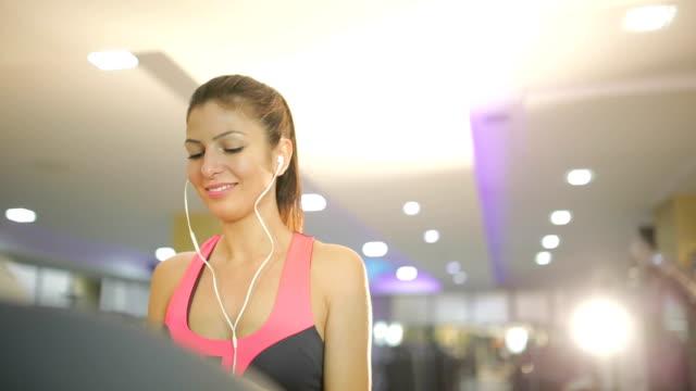 Lachende vrouw met smartphone op treademill