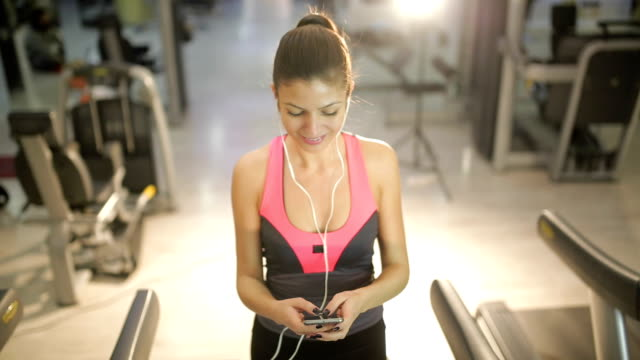 smiling woman with smartphone on treademill - treadmill stock videos & royalty-free footage