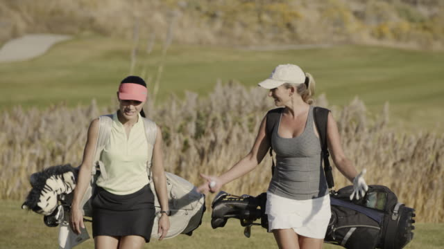 vidéos et rushes de smiling women carrying golf bags on golf course / cedar hills, utah, united states - enjoyment