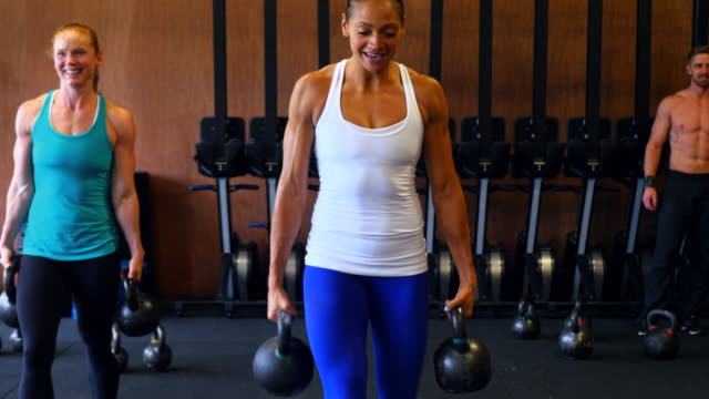 MS Smiling women carrying kettlebells during workout in gym gym