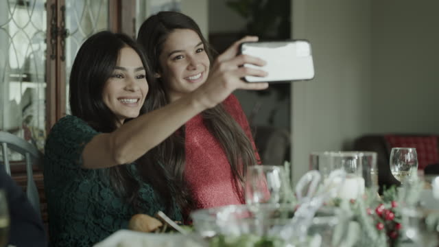 smiling women posing for cell phone selfie at dinner table / orem, utah, united states - orem stock videos & royalty-free footage