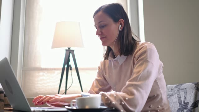smiling women replying to a text message while working on her laptop away from home - remote location stock videos & royalty-free footage