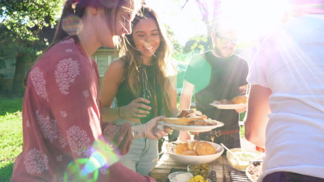 vidéos et rushes de ms pan smiling women serving themselves barbecue in backyard on summer evening - repas