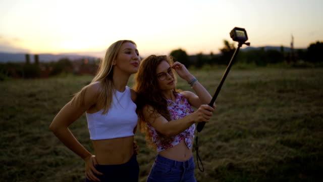 夕暮れ時に selfie を取っている笑顔の女性 - 自画像点の映像素材/bロール