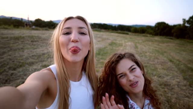 smiling women taking selfie at dusk - tongue stock videos and b-roll footage
