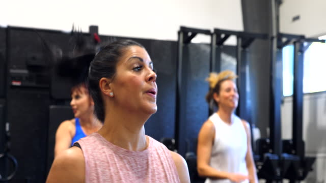 vídeos de stock, filmes e b-roll de pan smiling women working out in gym during fitness class - 40 49 anos