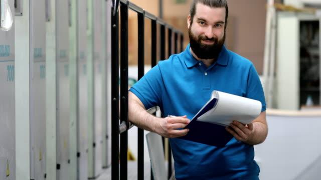 Lächelnde Arbeiter lesen Dokument an Druckerei