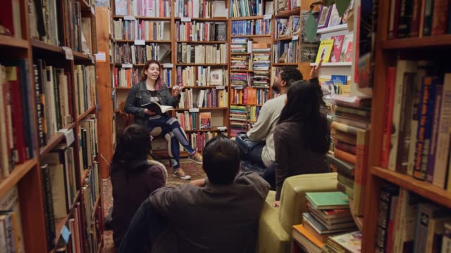 smiling writer giving a reading in a bookstore - bookstore stock videos & royalty-free footage