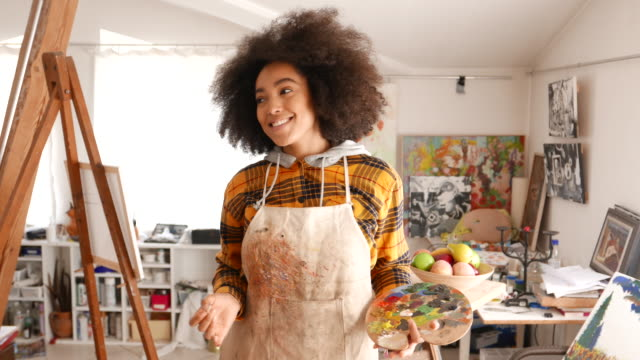 smiling young afro woman holding color palette and paintbrush - painter artist stock videos & royalty-free footage