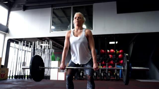 vídeos de stock, filmes e b-roll de atleta novo de sorriso que deixa cair um peso pesado - peso livre equipamento para exercícios