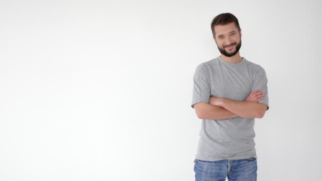smiling young bearded man pointing sideway, advertising something - touching stock videos and b-roll footage