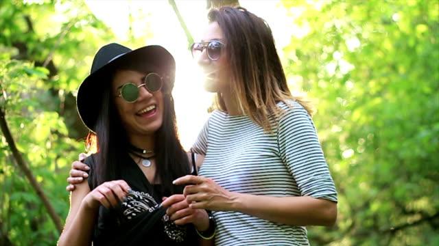 Lächelnde junge schöne lesbische Mädchen Informationstisch um in Natur