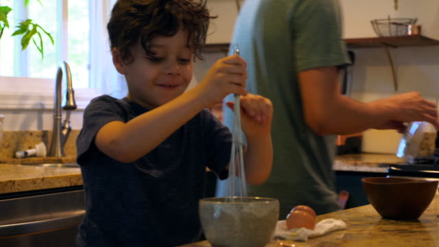 MS Smiling young boy and father making scrambled eggs together in kitchen