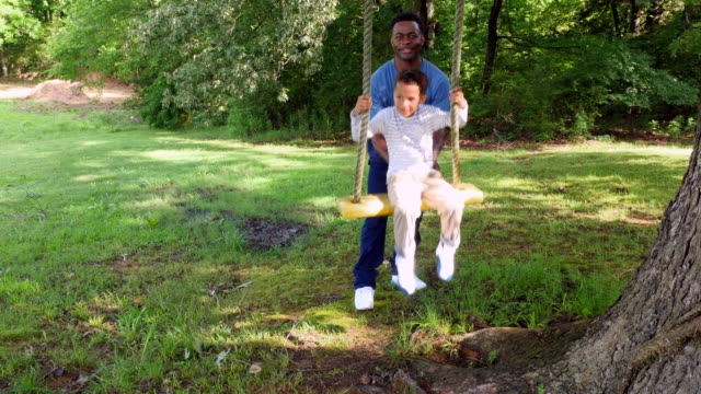 MS Smiling young boy being pushed on swing by father in backyard