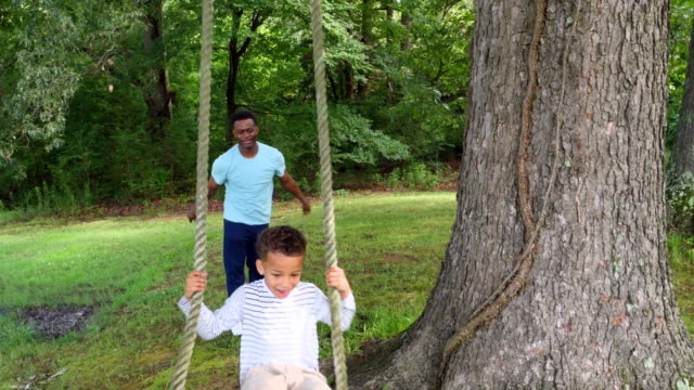 ms smiling young boy being pushed on swing by father in backyard - genderblend stock videos & royalty-free footage
