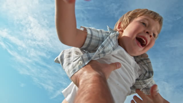 slo mo smiling young boy being tossed into the air in sunshine - exhilaration stock videos & royalty-free footage
