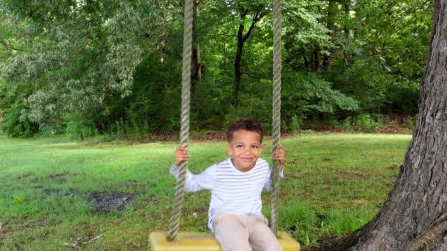 vídeos y material grabado en eventos de stock de ms smiling young boy on tree swing in backyard of home - columpiarse
