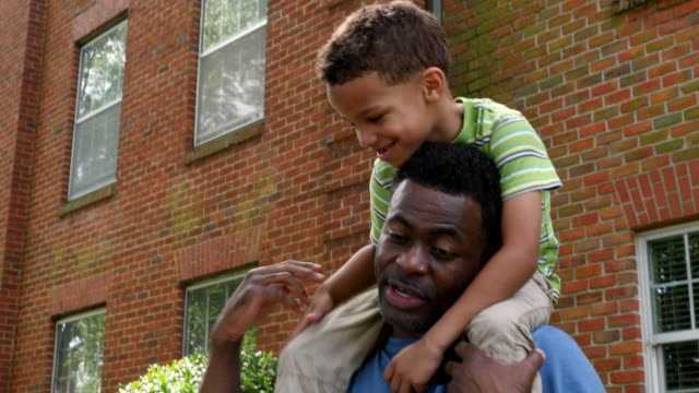 MS LA Smiling young boy riding on fathers shoulders on summer afternoon