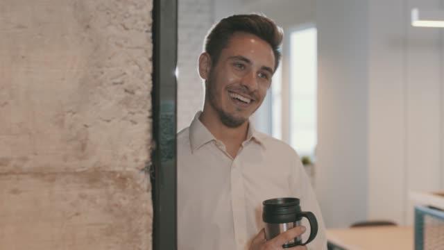 vídeos y material grabado en eventos de stock de joven empresario sonriente disfrutando del café y contemplando - taza de café