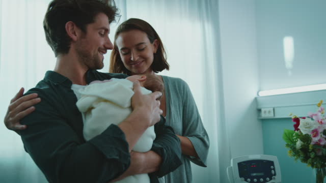 smiling young couple admiring newborn at hospital - unknown gender stock videos & royalty-free footage