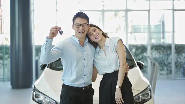 新しい車を買う笑顔の若いカップル - 車のキー点の映像素材/bロール
