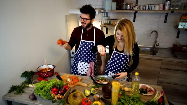 Lächelnde junge Paar Garen von Speisen in der Küche, schöner Mann Tomaten jonglieren
