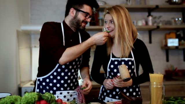 lächelnd junges paar garen von speisen in der küche - essen zubereiten stock-videos und b-roll-filmmaterial