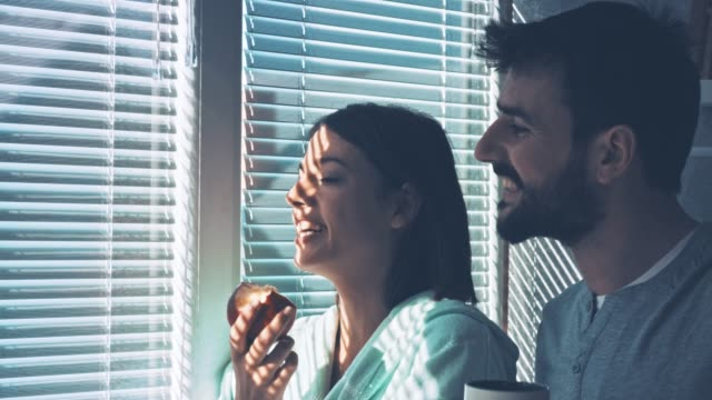 smiling young couple looking through the window in the morning - blinds stock videos & royalty-free footage