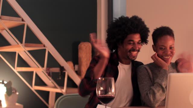 Jeunes couples de sourire faisant l'appel vidéo sur la main d'ondulation d'ordinateur portatif