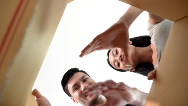smiling young couple opening a carton box and looking inside to catch something - box container video stock e b–roll