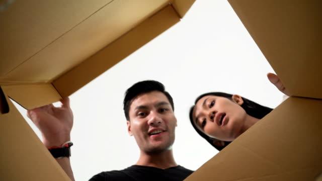 Lächelnd junges Paar einen Karton öffnen und Blick ins Innere