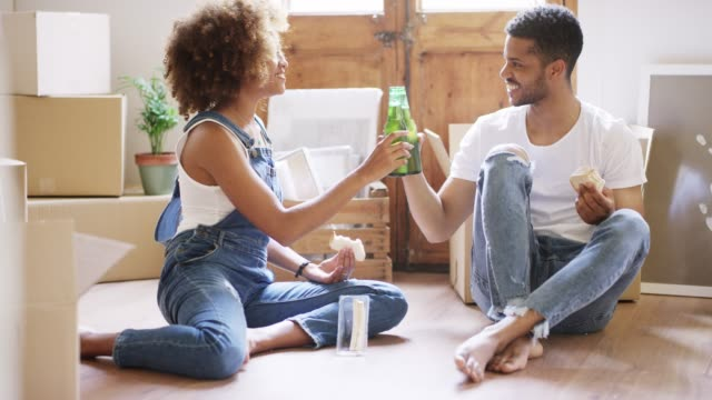 smiling young couple raising toast at new home - beer bottle stock videos and b-roll footage