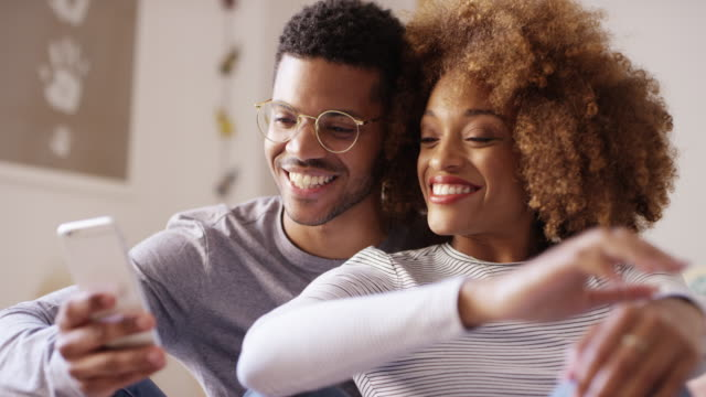 smiling young couple sharing smart phone at home - young couple stock videos & royalty-free footage