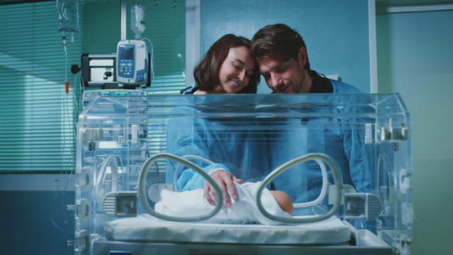 smiling young couple touching infant in incubator - delivery room stock videos & royalty-free footage