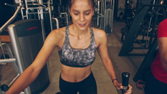 smiling young female athlete enjoying her workout on elliptical machine - exercise machine stock videos & royalty-free footage