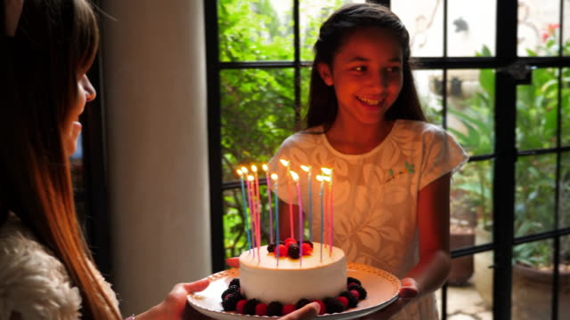 ts smiling young female cousins bringing birthday cake with candles to dinner table during family birthday party - birthday cake stock videos & royalty-free footage