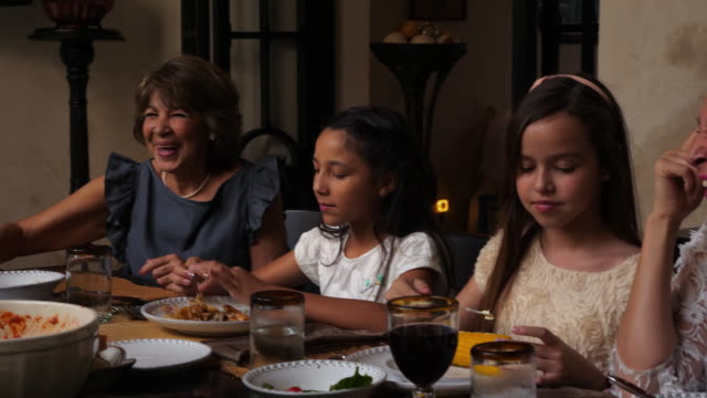 pan smiling young female cousins sitting next to aunt and grandmother while eating dinner together - dining table stock videos & royalty-free footage