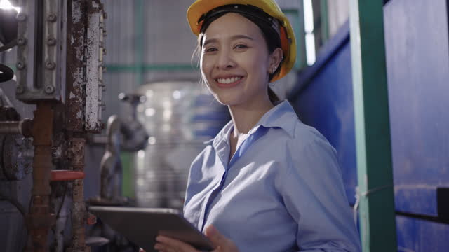 smiling young female operator in factory - video stock videos & royalty-free footage