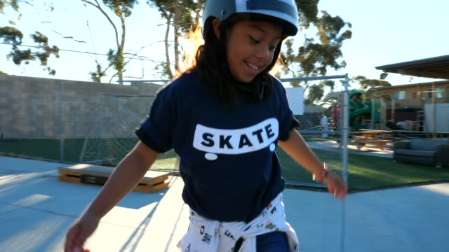 ts smiling young female skateboarder riding board in park during summer camp - summer camp stock videos & royalty-free footage