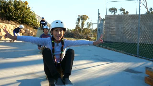 ts smiling young female skateboarder sitting on board during summer skate camp - helmet stock videos & royalty-free footage
