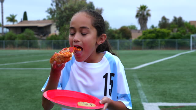 ms smiling young female soccer player eating slice of pizza after game - candid stock videos & royalty-free footage