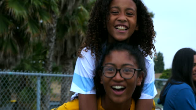 ms smiling young female soccer player riding piggy back on older sister after game - teenage girls stock videos & royalty-free footage