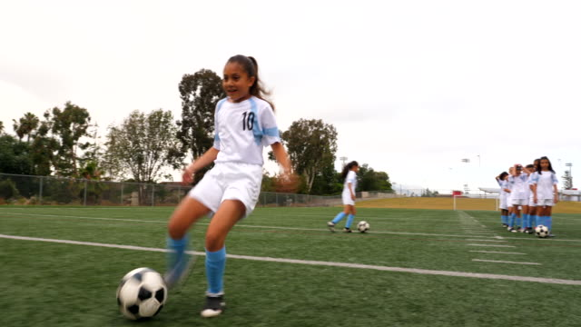 ms smiling young female soccer player taking shot while warming up before game - potere femminile video stock e b–roll