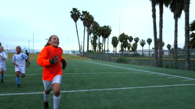 vídeos de stock, filmes e b-roll de ts smiling young female soccer players sprinting across field after game - jogador de futebol