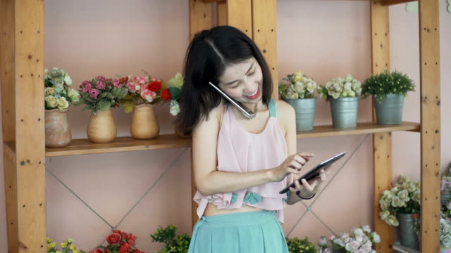 Lächelnde junge Floristin geschäftsfrau im Blumenladen machen und Dekorationen und floralen Arrangements für Ordnung und Blumen Lieferung arbeiten. Kleinunternehmer