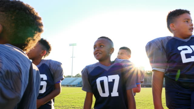 MS Smiling young football teammates gathered together on field for practice