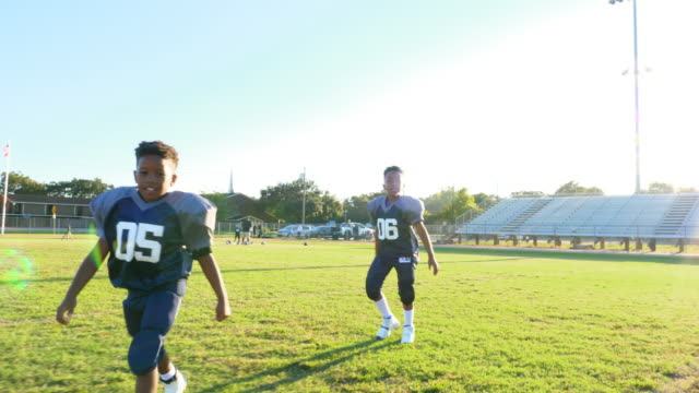 ms smiling young football teammates playing on field before practice - children only stock videos & royalty-free footage