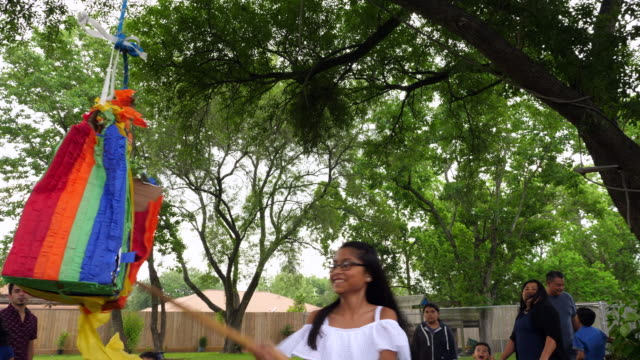 ms smiling young girl breaking open pinata during family birthday party - papier stock videos & royalty-free footage