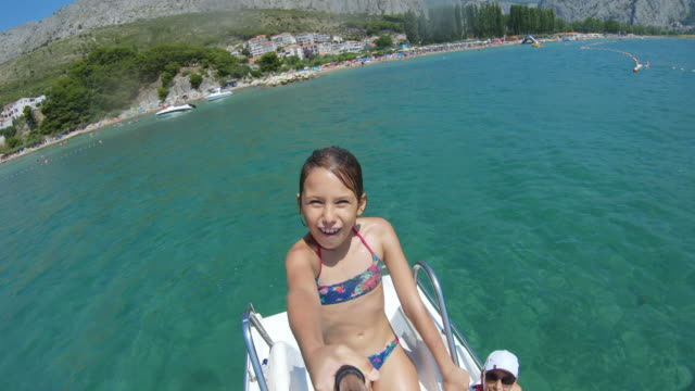 smiling young girl filming herself on pedal boat slide - sliding stock videos & royalty-free footage
